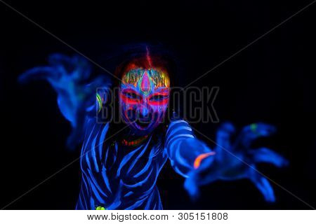 Close-up Portrait Of Wild And Frantic Young Naked Bodyarted Woman In Blue Glowing Ultraviolet Paint