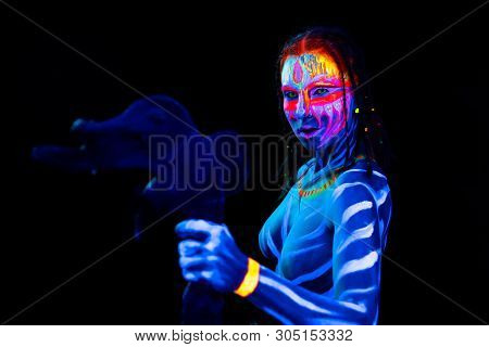 Portrait Of Young Naked Bodyarted Savage Woman In Blue Glowing Ultraviolet Paint With Primeval Prehi