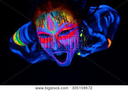 Close-up Portrait Of Young Naked Bodyarted Woman In Blue Glowing Ultraviolet Paint And Yellow Eye Le