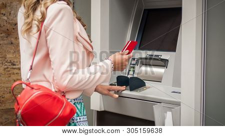 Woman Traveler Takes Out Money At An Atm In Europe