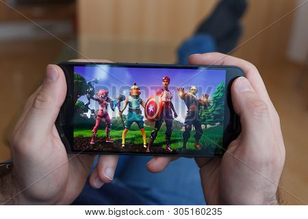 Los Angeles, California - June 3, 2019: Lying Man Holding A Smartphone And Playing The Fortnite Aven