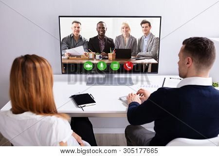 Rear View Of Businesspeople Video Conferencing With Their Partner On Computer At Workplace