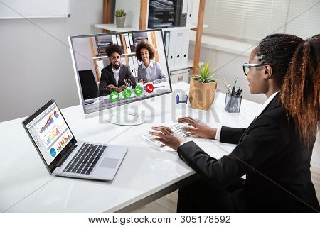 Smiling Young Businesswoman Videoconferencing With Her Colleagues On Computer Near Laptop