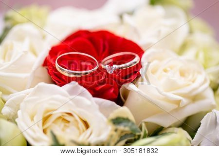 Wedding Ceremony. Two Golden Wedding Rings Laying On Tray Of Roses. Accessories For The Bride And Gr