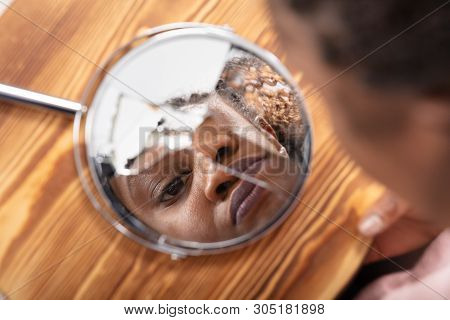 Close-up Of Young Woman Looking At His Face In A Broken Mirror