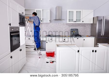 Rear View Of A Man Standing On Ladder Adjusting Cabinet Door Hinge On Kitchen Cabinet