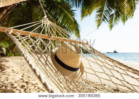 Close-up Of Sun Hat On Hammock Over The Sand At Beach