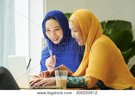 Pretty Young Muslim Women In Cafe Watching Lection Online On Laptop And Writing Down Main Ideas