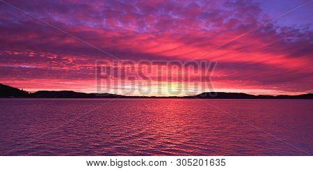 A Magnificent Panoramic Inspirational Magenta Coloured Altostratus Cloudy Sunrise Seascape Over Sea