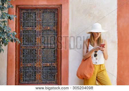 Stylish woman texting in traditional moroccan riad poster