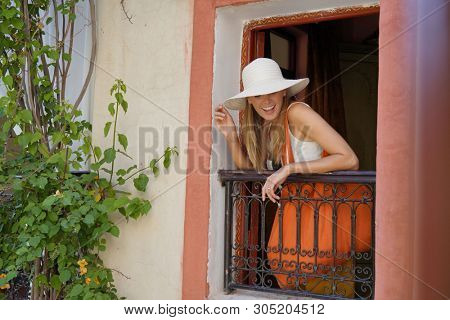 Stylish woman looking out traditioanl Moroccan window poster