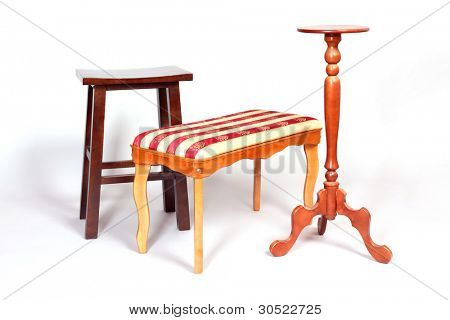 three beautiful wooden stools stand on white floor. simple, classic and ornate