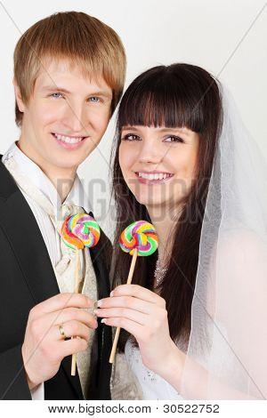glücklich junge Bräutigam und Braut halten bunte Lutscher auf weißem Hintergrund