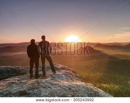 Hikers And Friends Stay On Cliff Within Dreamy Daybreak And Thinking. Dreamy Fogy Landscape Blue Mis