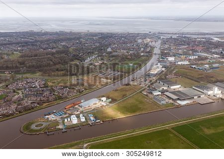 Aerial View Dutch Residential Area Delfzijl With Channel Eemskanaal And Industrial Park Near Harbor