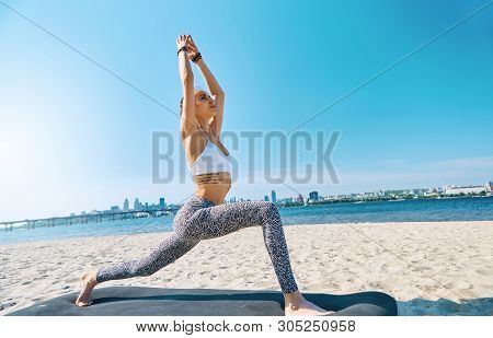 Outdoors Portrait Of Young Slim Athletic Woman Standing In Yoga Asana With Raised Hands On The City