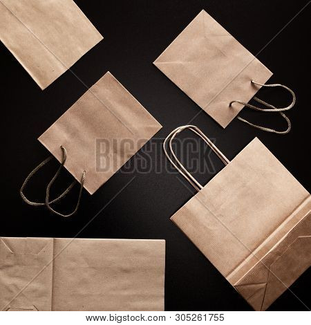 Paper Merchandise Bags On Black Background, Flat Lay