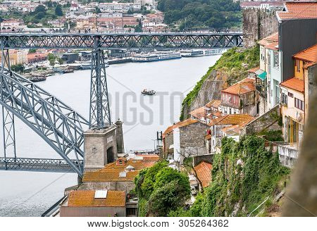 Roofs Of Porto City, Riverboats Sailing On The River Douro, And Famous Double-deck Metal Arch Bridge
