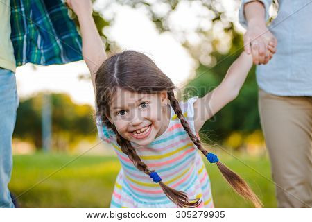 Little Girl Kid Daughter Holding Her Fathers Hand Background Nature Sunset. The Concept Of Parental