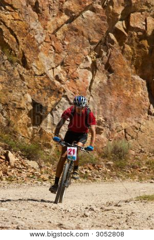 Mountain Biker Racing Near Rocks
