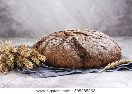 Freshly baked round sourdough bread and rye ears on kitchen table. Rustic style. Selective focus. Copy space poster