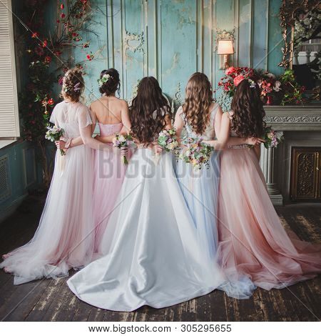 Bride And Bridesmaids. Beautiful Young Women In Dresses And With Bouquets Of Fresh Flowers. Back Vie