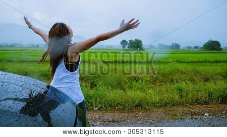 Asian Women Travel Relax In The Holiday.the Girl Smiled Happy And Enjoyed The Rain That Was Falling.