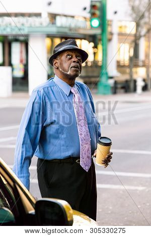 Handsome Senior Man Wearing A Hat Downtown Looking Up