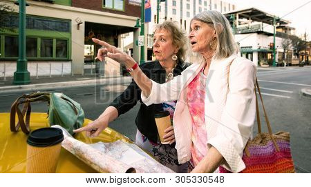 Two Women In A City Center With A Road Map