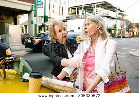 Two Women In A City Center Consulting A Confusing Road Map