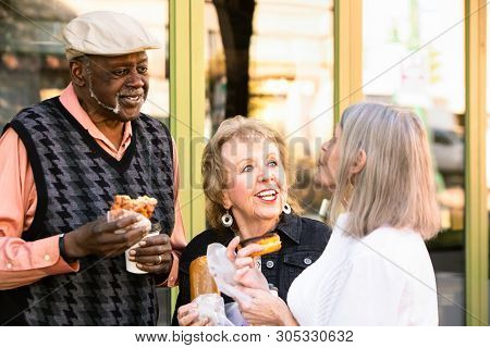 Three Seniors Friends Eating Donuts And Talking