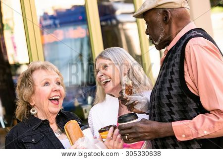 Three Seniors Downtown Eating Donuts And Laughing