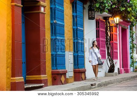 Beautiful Woman On White Dress Walking Alone At The Colorful Streets Of The Colonial Walled City Of