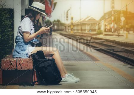 Tourist Women Holding Looking For Smartphone With Backpack Waiting For Train At Station In The Eveni