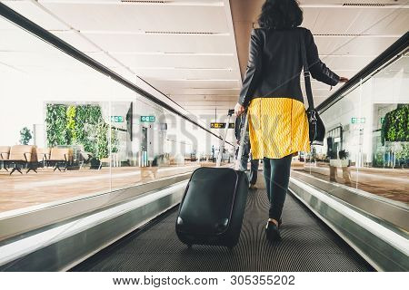 Woman Traveller With Travel Suitcase Or Luggage Walking In Airport Terminal Walkway For Vacation Tra