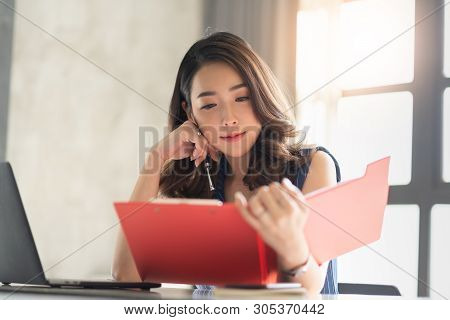 Portrait Of Smiling Pretty Young Business Woman Holding And Looking At A Red Clipboard, Document Fol