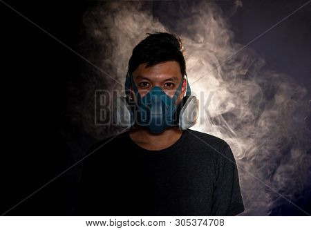 Man In A Gas Mask Smokes And Breathes A Cloud Of Tobacco Smoke ,black Background