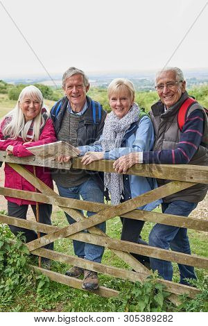 Portrait Of Group Of Senior Friends Hiking In Countryside Standing By Gate
