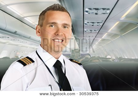 Airline pilot wearing uniform with epaulettes on board of passenger aircraft. poster