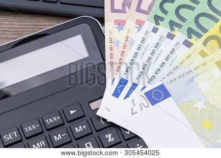 The Image Shows Some Banknotes On A Keyboard And A Calculator