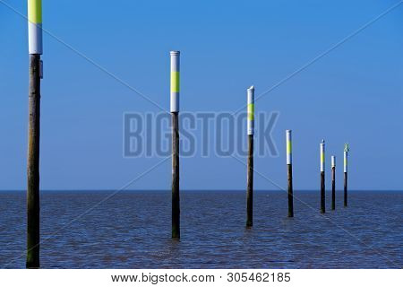 Wooden Poles In The North Sea Against Clear Blue Sky. Sankt Peter-ording Beach, Germany
