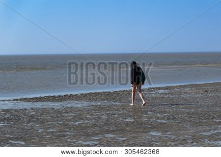 Woman In A Black Coat And With Bare Legs Is Walking On A Beach. Sankt Peter-ording In Northern Germa
