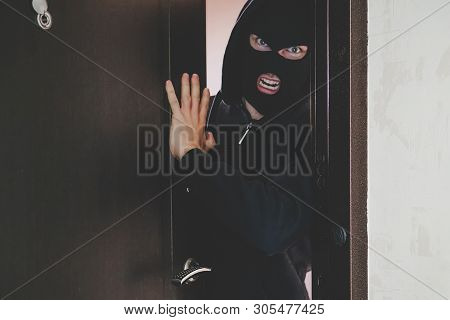 An evil gangster in a black mask covering his face broke the door and broke into the room and threatens the residents. concept of crime and violence. banditry, gangsterism, , racketeering, banditism, poster
