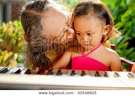 Ethnic Child And Grandma Playing Piano Together