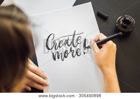 Creat More. Calligrapher Young Woman Writes Phrase On White Paper. Inscribing Ornamental Decorated L