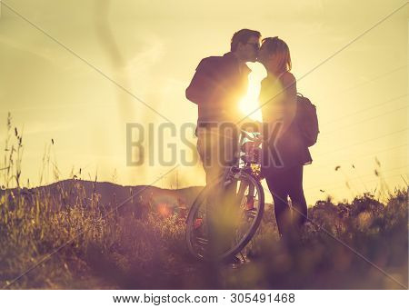 Young couple with bike is kissing on a field, sundown poster
