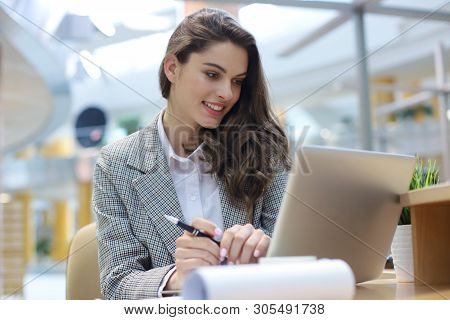 Portrait Of A Young Blond Business Woman Using Laptop At Office.