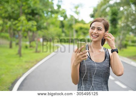 Young Woman Using Phone For Listening To Music. Fitness Runner Girl Listening To Music With Earphone