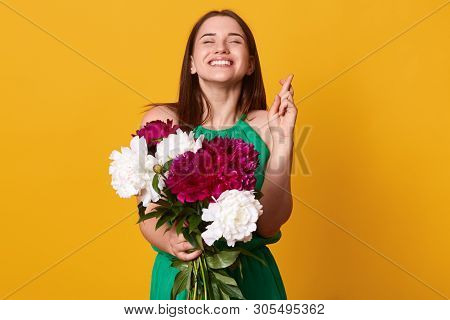 Stidio Shot Of Pretty Caucasion Woman Raises Crossed Fingers, Prays For Good Luck, Has Pleased And H
