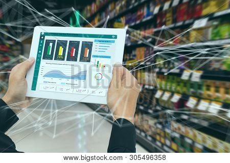 Iot Smart Retail In The Futuristic Concept, The Retailer Hold The Tablet And Use Augmented Reality T